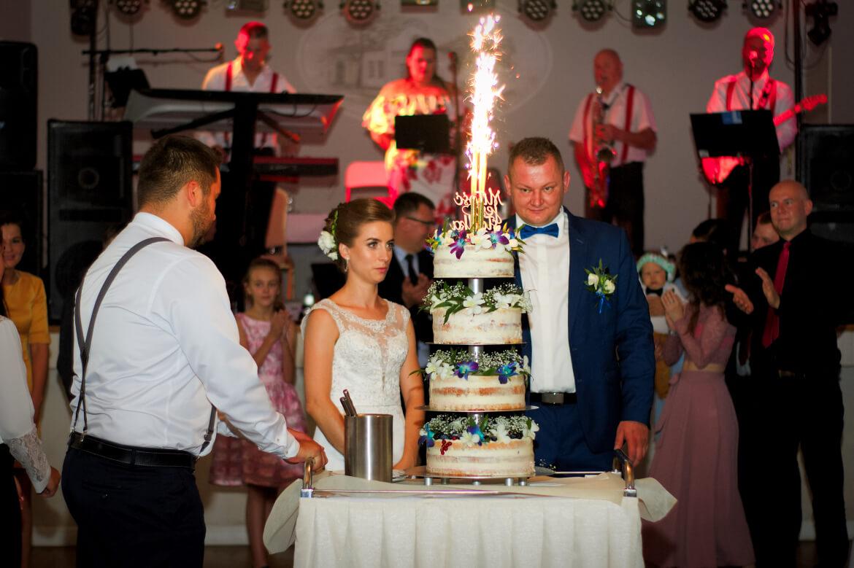 Fotografia ślubna. Młoda Para z płonącym tortem weselnym