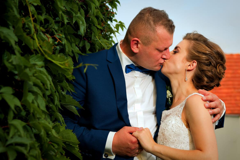 Fotografia ślubna. Pocałunek Młodej Pary przed salą weselną
