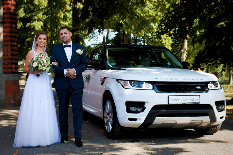 Ślub i wesele. Młoda para przy aucie